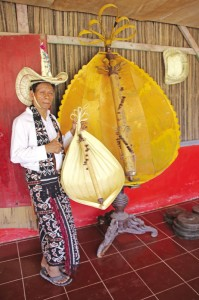 Jeremias in the traditional outfit with an acoustic sasandu and a giant replica