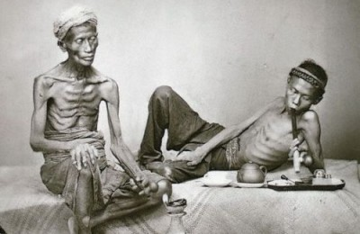 ca. 1840-1930, Java, Indonesia --- Two men smoke opium in Java, Indonesia. --- Image by ©Sean Sexton Collection/CORBIS