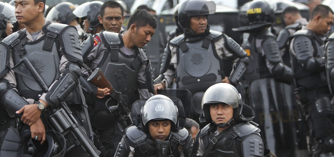 """Indonesian police officers in riot gears take a break during a show of force ahead of Christmas celebrations in Jakarta, Indonesia, Friday, Dec. 20, 2013. Since the Bali bombings in 2002, the world's largest Muslim country has been battling terrorists who recently operate in small groups and have targeted security forces and local """"infidels"""" instead of Westerners. (AP Photo/Tatan Syuflana)"""