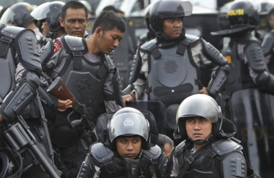 "Indonesian police officers in riot gears take a break during a show of force ahead of Christmas celebrations in Jakarta, Indonesia, Friday, Dec. 20, 2013. Since the Bali bombings in 2002, the world's largest Muslim country has been battling terrorists who recently operate in small groups and have targeted security forces and local ""infidels"" instead of Westerners. (AP Photo/Tatan Syuflana)"