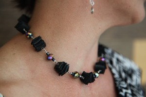 Samantha Beach wearing jewellery made out of trash. She is teaching wives of trash pickers in Ciledeu this skill.