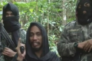 Santoso (middle) threatening the police through a YouTube video