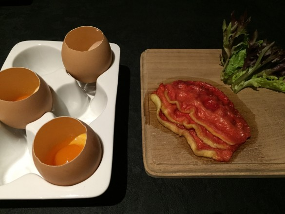 """A plate of what appeared to be a few slices of sukiyaki-style slices of raw beef paired with raw eggs served in their own shell"""