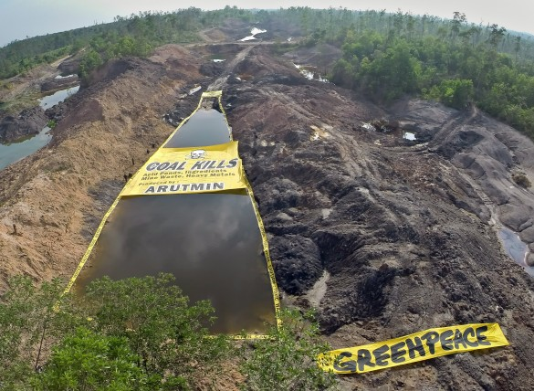 "Greenpeace activists unfurl a banner reading ""Coal Kills. Acid Ponds Ingredients: Mine Waste, Heavy Metals Produced by: Arutmin"", at the Asam-asam Coal Mine in South Kalimantan, which is scarred with toxic settling ponds used by the coal industry. The activists also surround the pond with 'Caution: Toxic Water' tape. Greenpeace is calling on the provincial and national government to stop the coal industry poisoning the water sources and local environment that communities rely on."