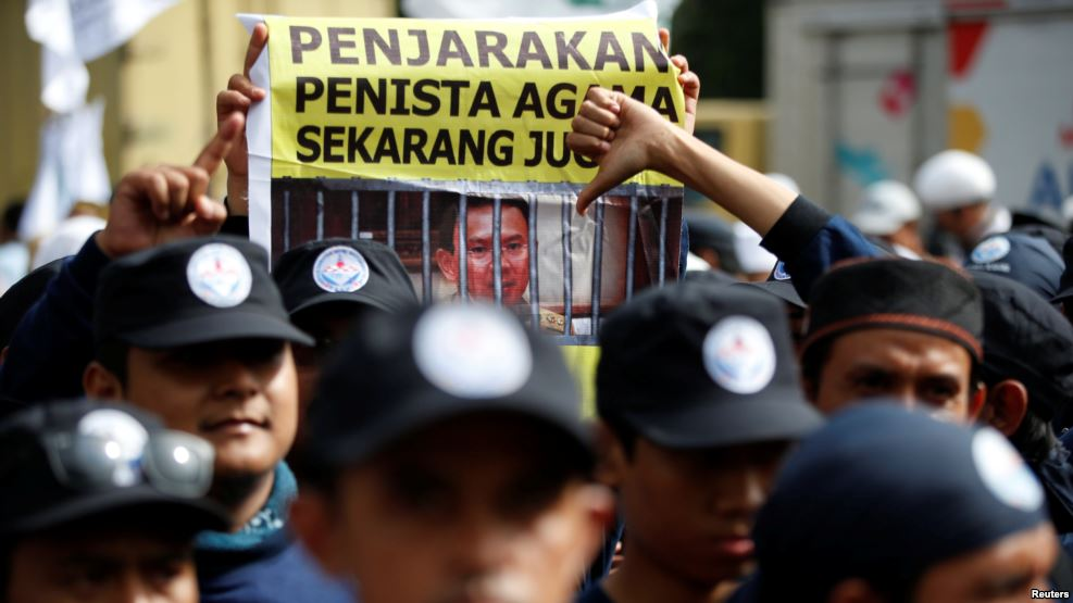 A protest banner against Governor Ahok is raised during the first day of the governor's trial.
