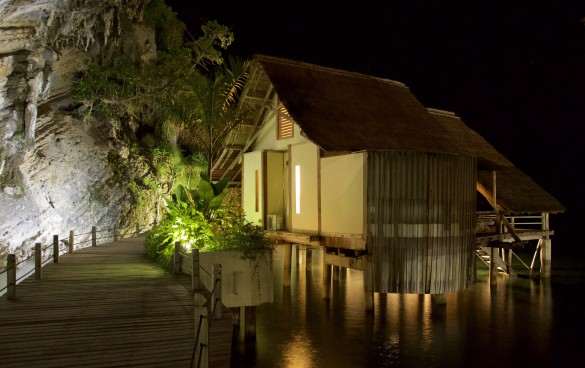 A waste water garden glows in the warm light of Misool's boardwalk and Water Cottages