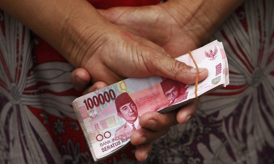 Woman holds cash in Rupiah on her hands