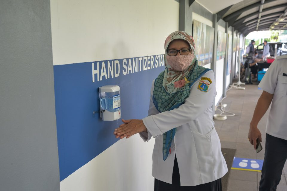 Head of the Central Jakarta II Education Office using a hand sanitizer at the Cilandak, JIS campus during her visit to trial limited school opening.